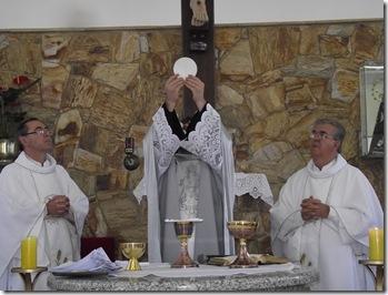 A imagem demonstra o sacerdote e ao seu lado lado os ministros extraordinários.
